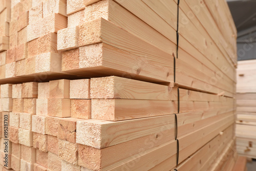 Many folded wooden planks in a warehouse with a forest - 195287103