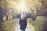 Back view of a woman walks in the sunny autumn season park. Selective focus used. - 195291902