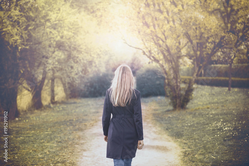 Back view of a woman walks in the sunny autumn season park. Selective focus used.