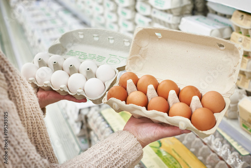 Woman with packs of white and brown eggs in store