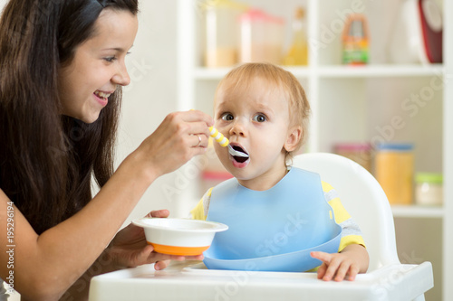 Mother feeding her baby with spoon. Mother giving healthy food to her adorable child at home - 195296194