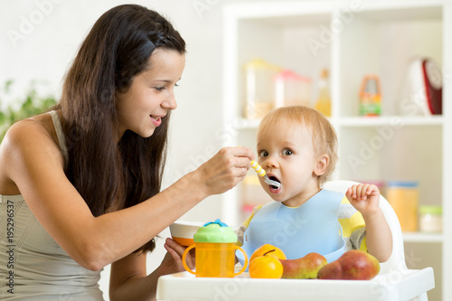 Mom giving homogenized food to her baby son on high chair in kitchen. - 195296537
