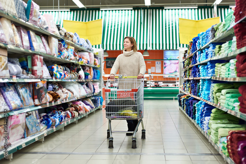 Woman shopper with trolley product chooses products in shop