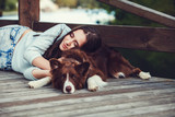 Beautiful woman lying with her dog. Outdoor portrait.