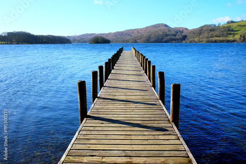 Fotobehang Pier very long wooden symetrical beautiful wooden jetty, jutting out from the centre of the image into a calm blue lake with hills of forest and meadows in background