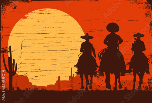 Fototapeta Silhouette of three Mexican cowboys riding horses on a wooden board
