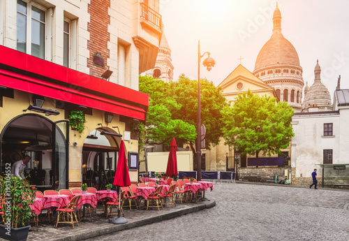 Fototapeta Cozy street with tables of cafe in quarter Montmartre in Paris, France