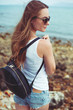 side view of young woman in sunglasses with backpack with ocean on background
