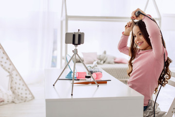 Fancy locks. Sweet pre-teen girl curling her hair with the help of a curling iron and smiling at the camera while recording a hairstyle tutorial for her video channel