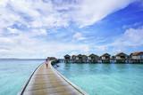 Female tourist walking on the bridge to luxury water villas in tropical Maldives island - 195309594
