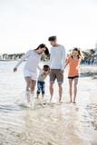 Familie mit 2 Kindern beim Strandspaziergang - 195316534