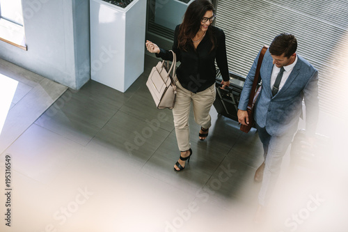 Business people arriving at hotel with luggage
