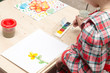 A girl draws a drawing with paints on a sheet