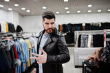 Stylish turkish man at the store of fur coats and leather jackets. Successful arabian beard man. - 195317307