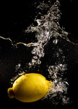 Yellow lemon in water on a black background