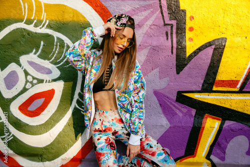 Fotobehang Graffiti Young stylish woman, dressed in bright suit, cap, in sunglasses, standing on a graffiti wall background. Outdoors.