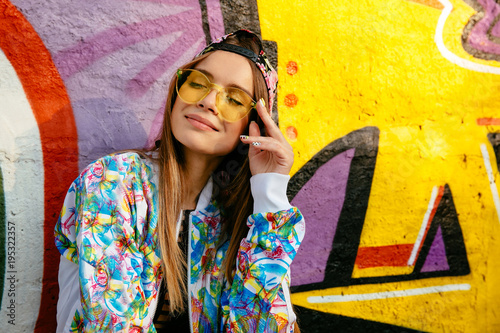 Aluminium Graffiti Charming pretty girl in eyeglasses, closed her eyes, enjoying leisure, standing near the wall with art graphics. Dressed in colorful jacket and cap. Outdoors.