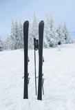 Skis and sticks stuck in snow on mountain peak