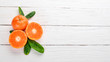Fresh mandarin with leaves. Fruits. On a wooden background. Top view. Copy space.