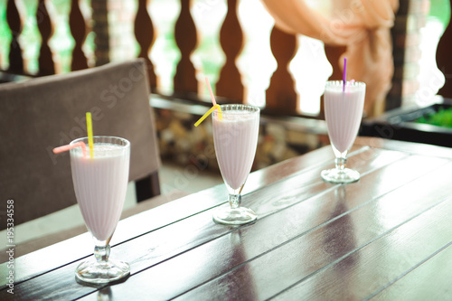Foto op Plexiglas Milkshake Three jars of pink berry milkshakes with straws on old wooden table