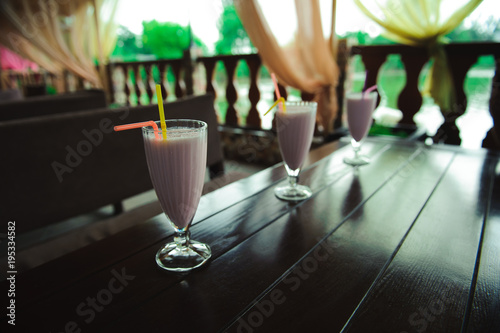 Keuken foto achterwand Milkshake Three jars of pink berry milkshakes with straws on old wooden table