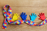 Autism awareness concept with colorful hands on wooden background. Top view