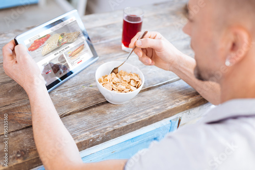Nutritious treat. Skillful ambitious man eating healthy granola while taking spoon and studying article about biohacking
