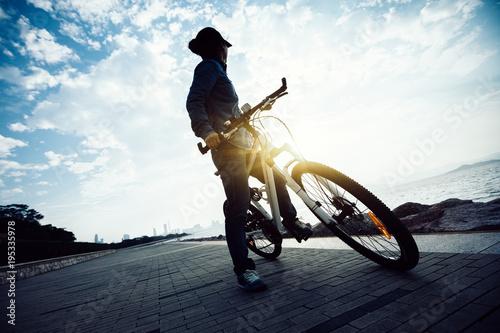 rowerzysta patrząc na wschód słońca podczas jazdy rowerem w ścieżce wschód słońca wybrzeża