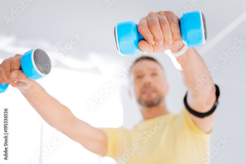 Self improvement. Selective focus of blue useful dumbbells hold by bearded man who training with biohacking