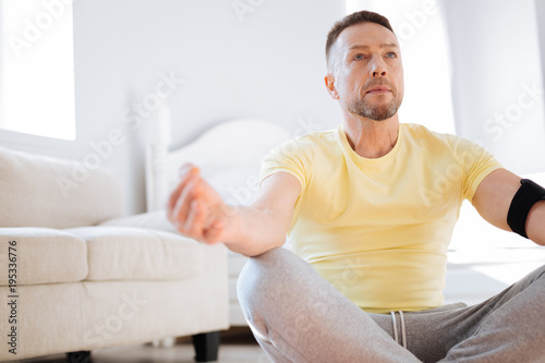 Benefits of mediation. Handsome earnest confident man looking straight while calming down and meditating