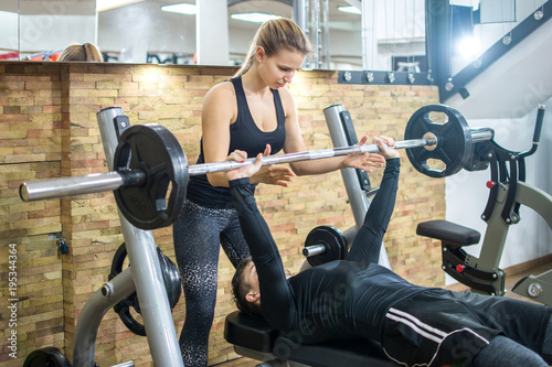 Handsome young man lifting weights with assistance of attractive girl in health club.