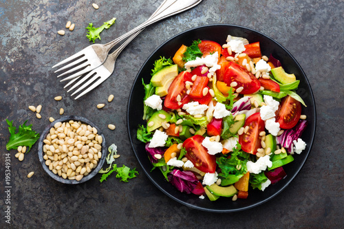 Vegetable dish, salad with avocado, pepper, tomato, italian mix, fresh lettuce, feta cheese and pine nuts. Healthy food. Top view - 195349314