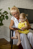 Grandmother and little girl reading book happy together at home - 195354339