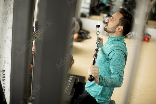 Man doing excersise on a lat machine in gym