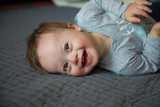 Portrait of cute baby boy with Down syndrome on the bed in home bedroom - 195357123