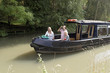 Holidaymakers aboard a narrowboat on the Wilts and Berks Canal near Swindon Wiltshire UK.