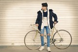 young to the fashion with the bicycle in the street of the city - 195369143