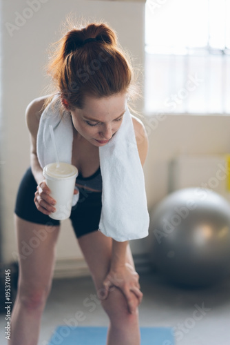 Fit young woman holding coffee in a gym