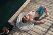 beautiful small child with sunglasses sunbathing in summer sun lying on old wooden pier