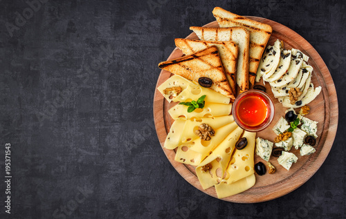 Cheese plate: Parmesan, cheddar, gouda, mozzarella and other with basil on wooden board on dark background with place for text.Honey and Crackers