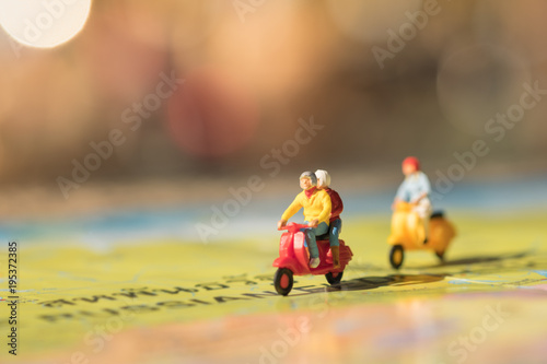 Keuken foto achterwand Scooter Travel Concept. Group of traveler miniature figures ride motorcycle / scooter on world map.