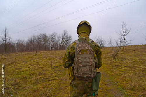 Rear view of military man outdoors in the field. Poster