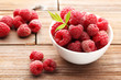 Ripe raspberries in bowl on brown wooden table