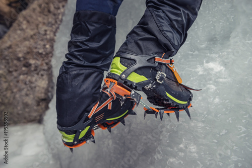 Foto op Canvas Natuur Climber on a frozen waterfall. Crampons close-up on his feet ice climber