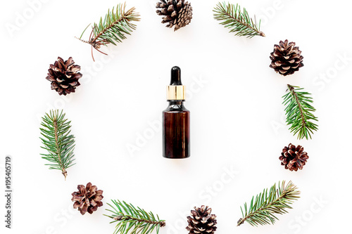 Pine essential oil in bottles on white background top view. Pattern with pine branch and cone © 9dreamstudio