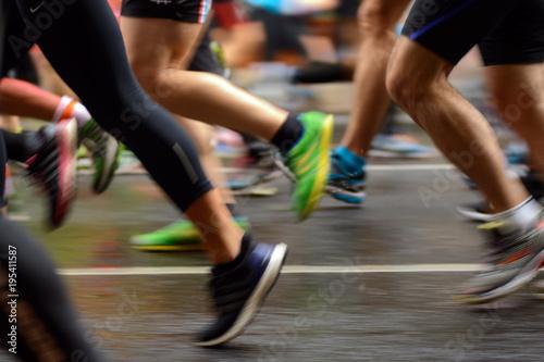 Fototapeta Male and female runner's legs on asphalt. Marathon