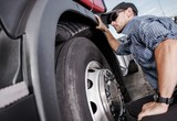 Trucker Making Tire Check - 195411774