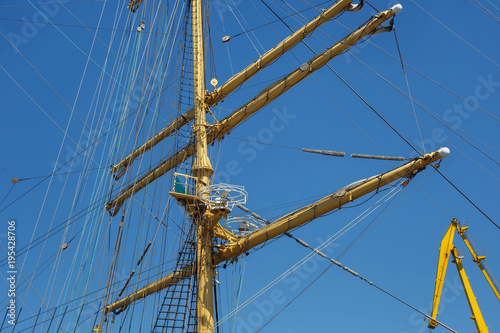 Keuken foto achterwand Schip Masts of a sailing ship with the lowered sails with blue sky on the background.