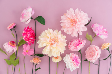 Crepe paper flowers on pink wooden background