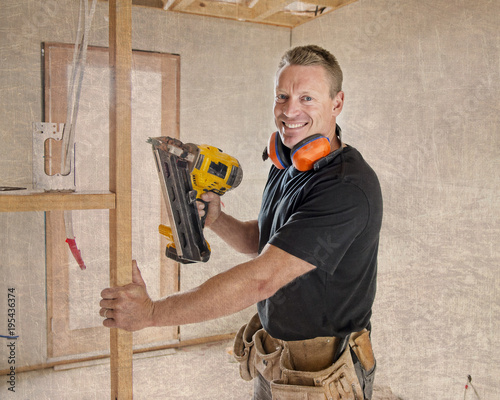 confident constructor carpenter or builder man working wood with electric drill at industrial construction site in installation and renovation work industry